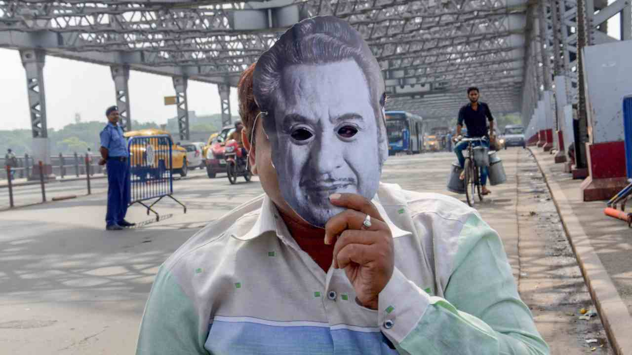 A person sports a mask of the legendary singer Kishore Kumar to pay tribute during his 89th birth anniversary at Howrah Bridge, in Kolkata. (PTI)
