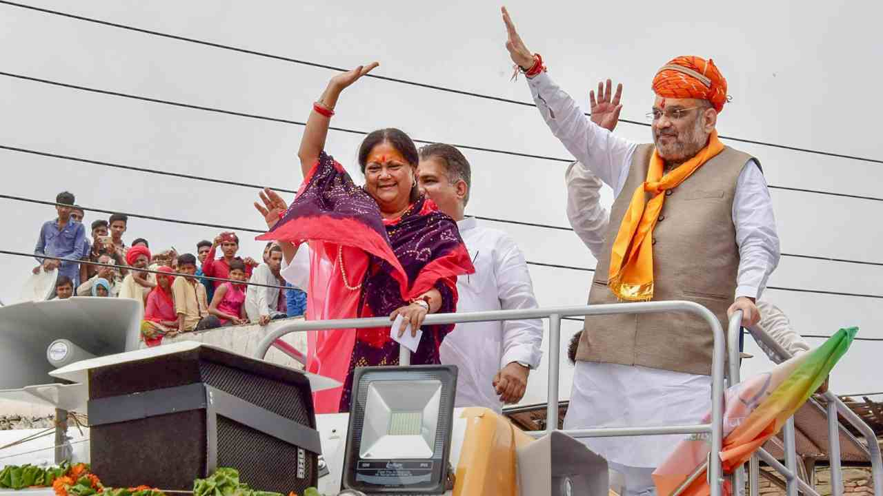 BJP President Amit Shah with Rajasthan Chief Minister Vasundhara Raje wave at their supporters during a public meeting to start 'Suraj Gaurav Yatra' at Charbhuja. (PTI)