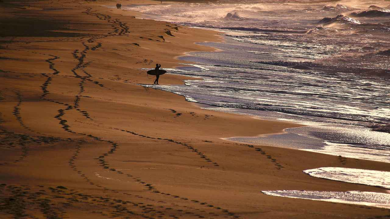 People walk along the beach as a surfer holding his board looks at the waves on Merewether Beach in Newcastle, located north of Sydney, Australia. (Reuters)