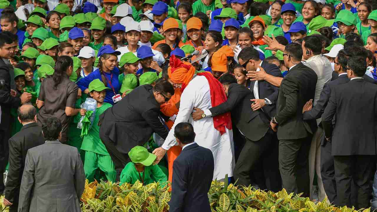PM Modi extends help to a child who slipped during his interaction with children, after addressing the nation on Independence Day at the Red Fort, in New Delhi. (PTI)