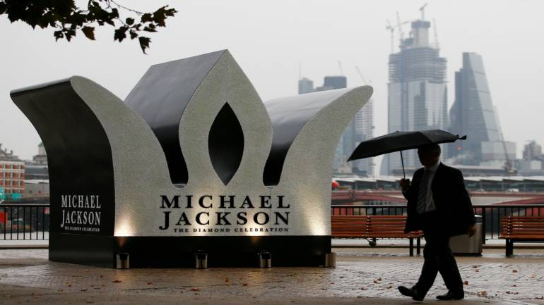 A man walks past a Giant Crown installed to celebrate the 60th birthday of Michael Jackson, on the South Bank in London, Britain on Wednesday. Image Source: Reuters.