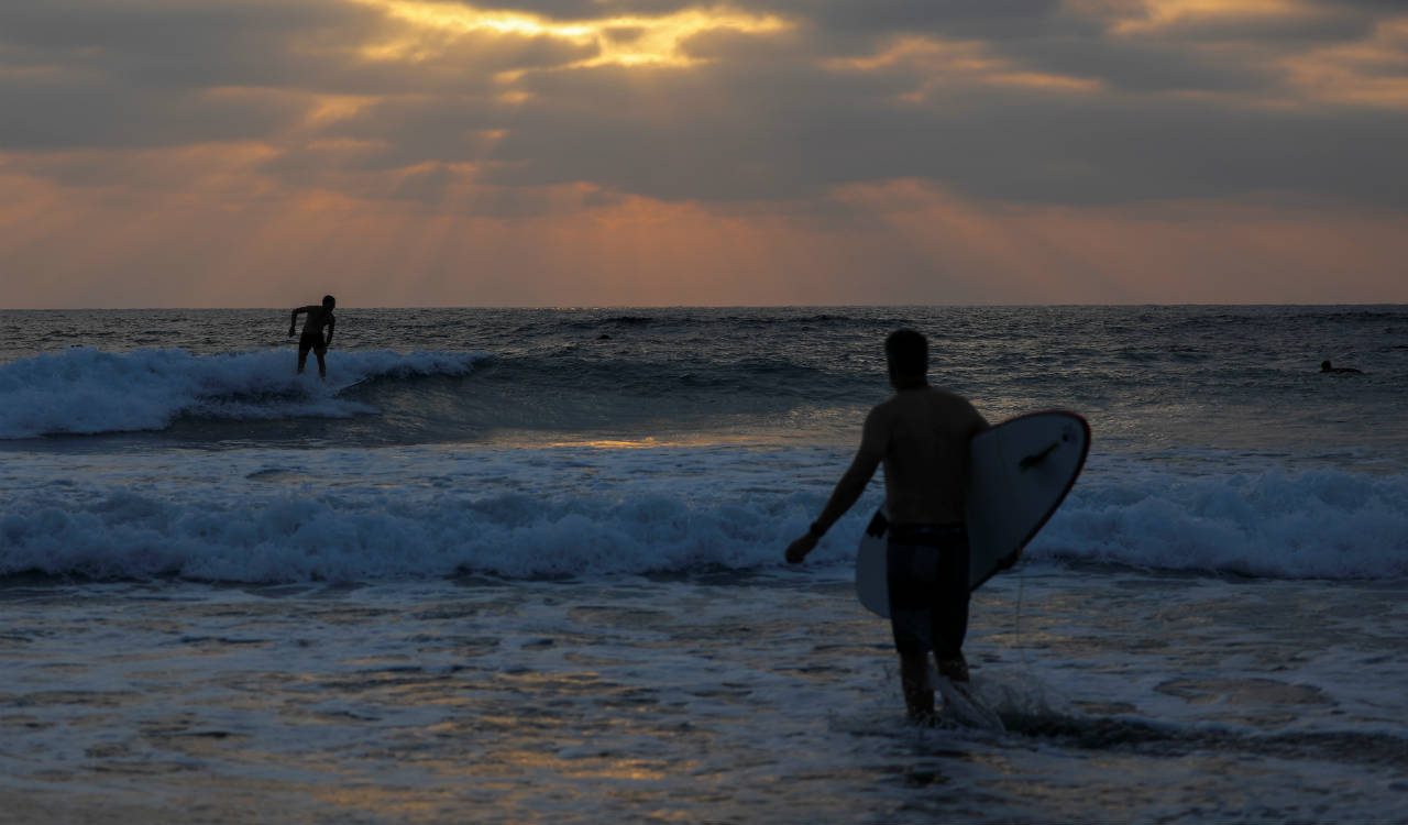 The same day California governor Jerry Brown signs a bill declaring surfing the official sport of California, surfers catch some of the last waves before sunset at Cardiff State Park in Encinitas, California, U.S. (Reuters)