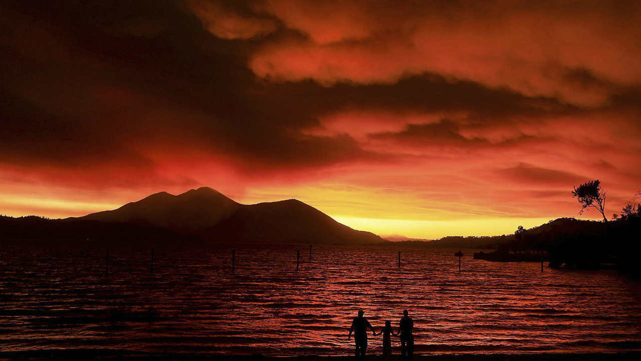 Evacuees from Lucerne, from left, Ken Bennett with Ember Reynolds, 8, and Lisa Reynolds watch the sunset as smoke from the Ranch Fire rises into the sky at Austin Park Beach in California's Clearlake with Mount Konocti in the background. (PTI)