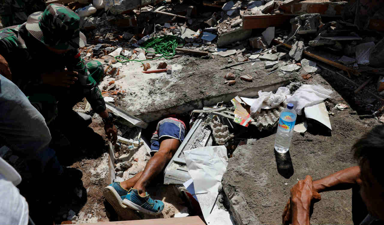 A volunteer crawls beneath rubble while soldiers try to find survivors at a collapsed house after earthquake hit on Sunday in Pemenang, Lombok Island, Indonesia