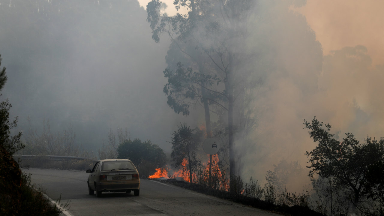 A car passes next to a fire near small village of Monchique, Portugal. (Photo: Reuters)