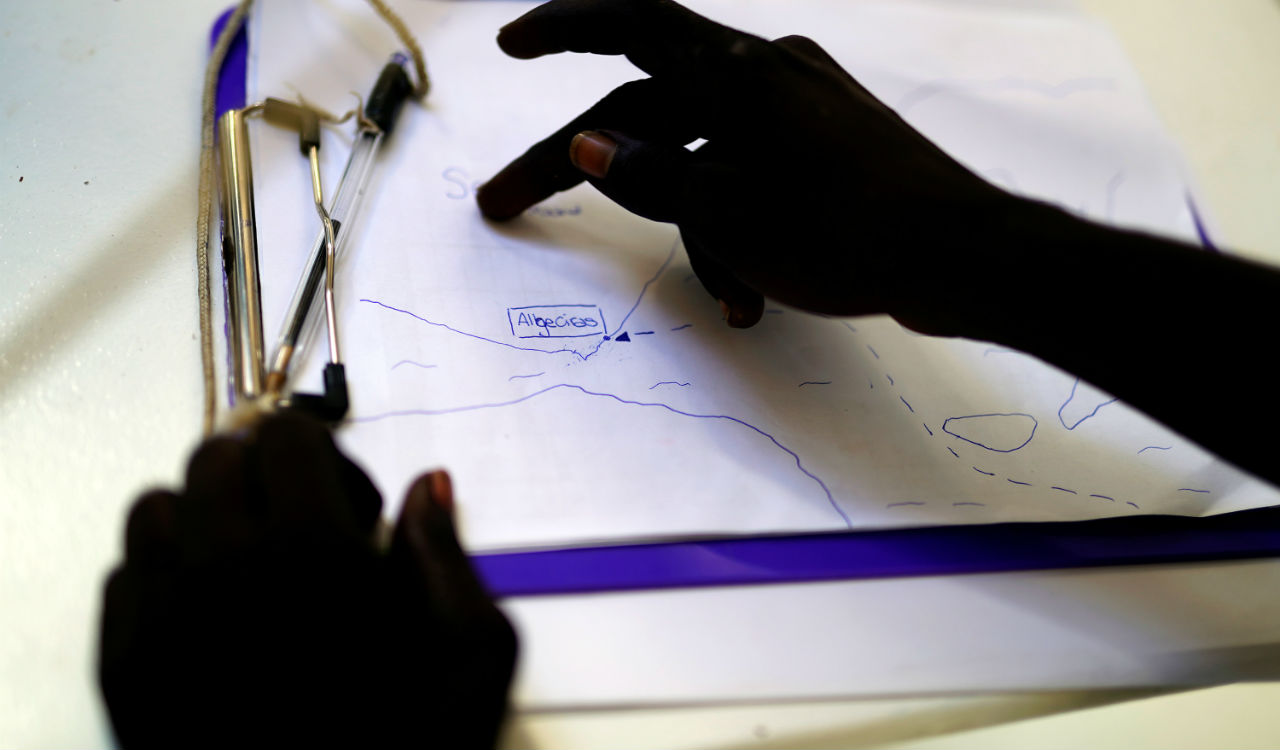 A migrant looks at the location of the port of Algeciras on a handmade map by Open Arms crew on board NGO Proactiva Open Arms rescue boat in central Mediterranean Sea. (Reuters)