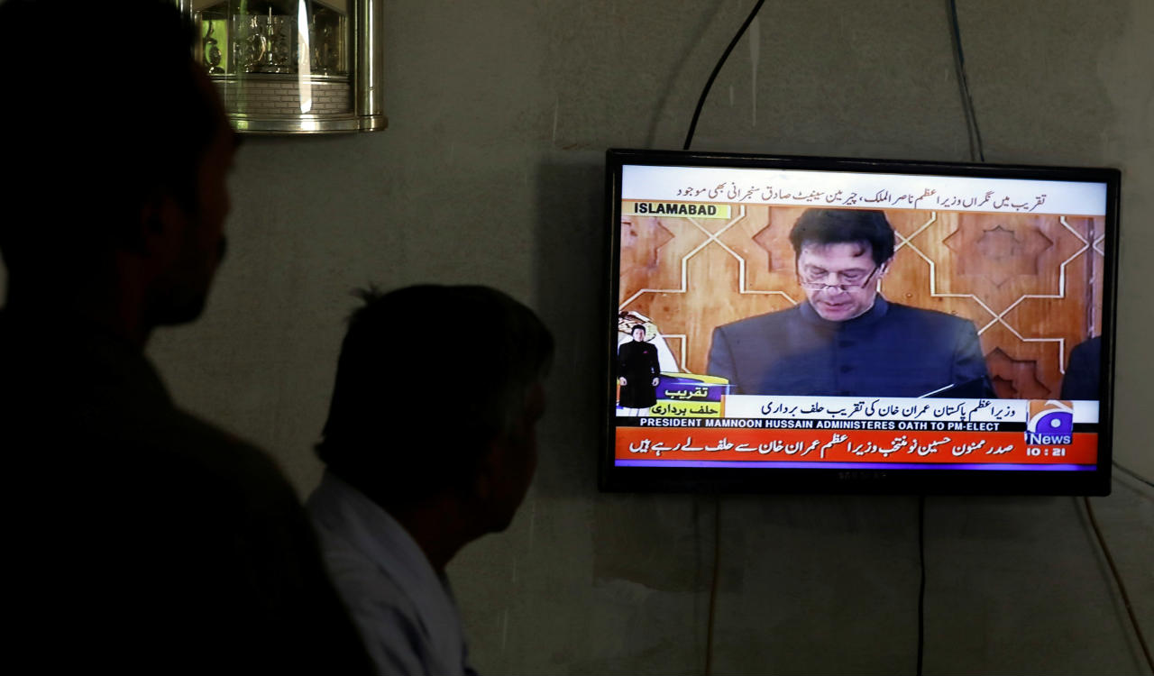 Men look at a television screen displaying cricketer-turned-politician Imran Khan swearing in as Prime Minister of Pakistan, in Karachi, Pakistan. (Reuters)