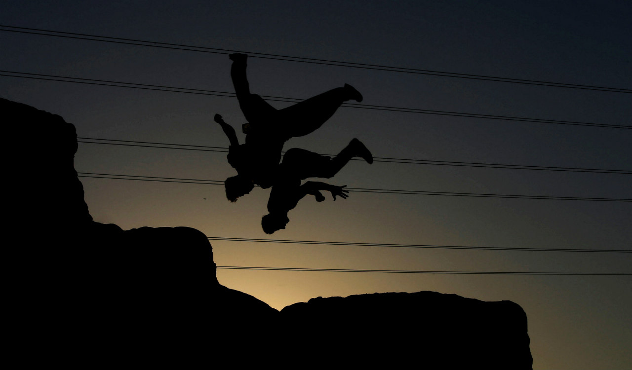 Iraqi youths perform a somersault as they practice parkour in the city of Najaf, Iraq. (Reuters)