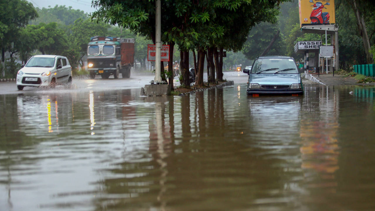 Vehicles make their way through a waterlogged road after rainfall, in Jammu. (Photo: PTI)