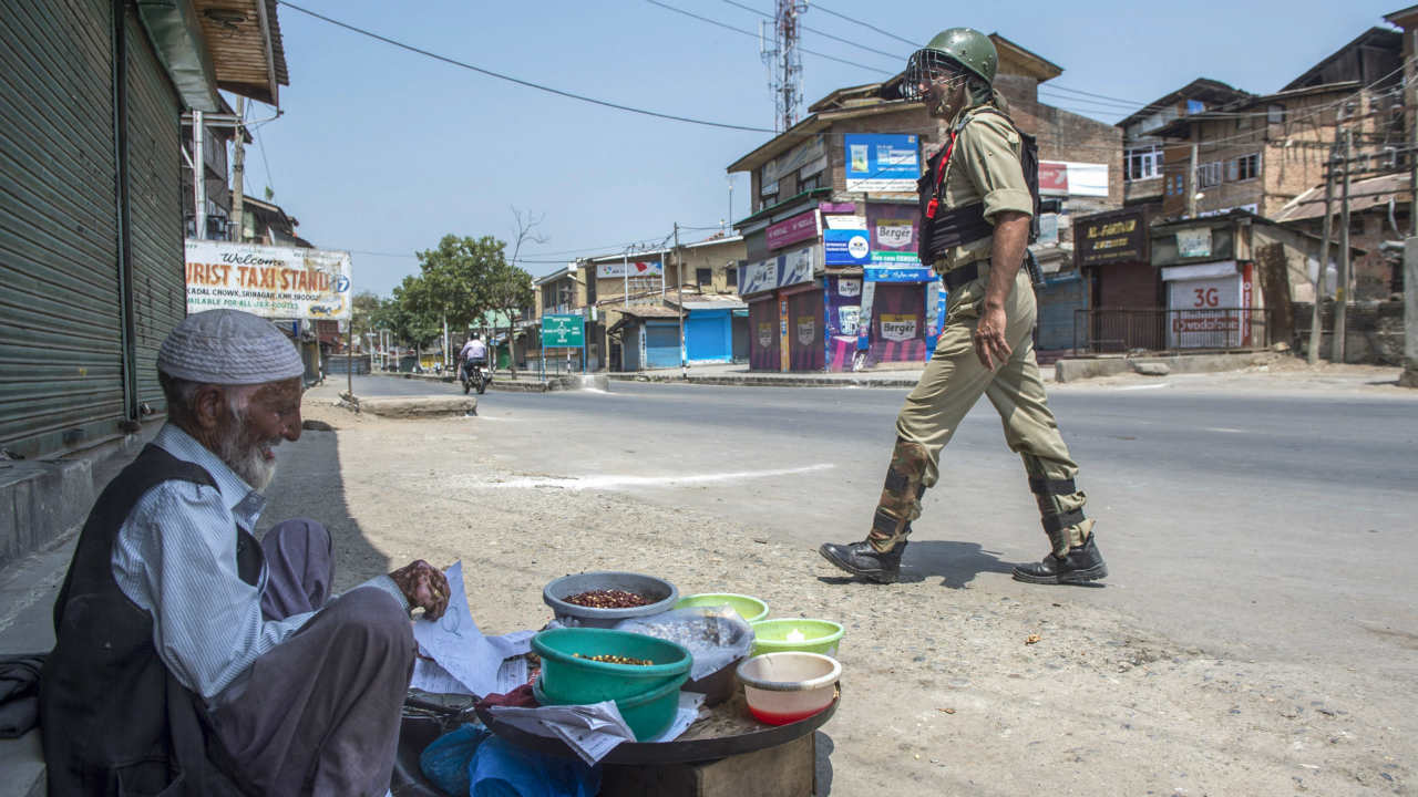 A security personal walks past a vendor during the second day of strike called by separatist leaders against the petitions filed in the Supreme court challenging the validity of Article 35A, in Srinagar. (Photo: PTI)