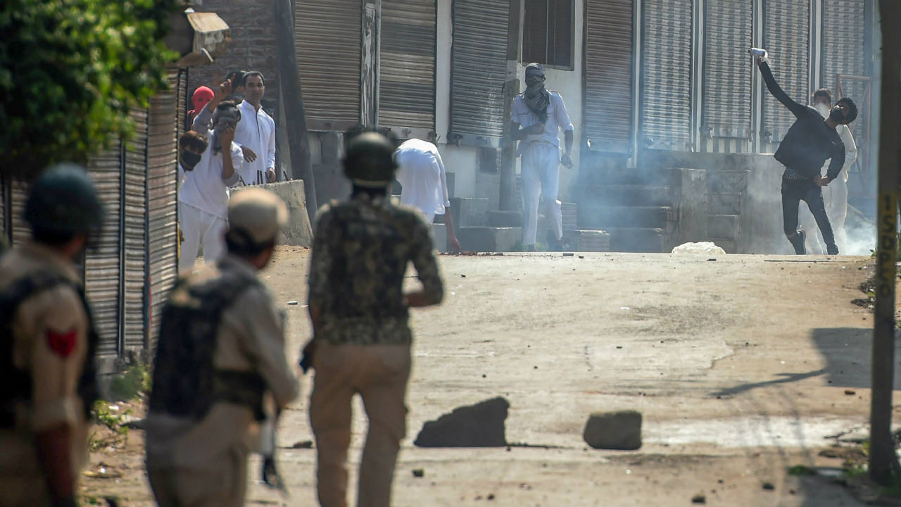 Protesters throw stones at security personnel amid heavy tear smoke during clashes which erupted at a protest march soon after the Eid al-Adha prayers, in Srinagar. (Image: PTI)