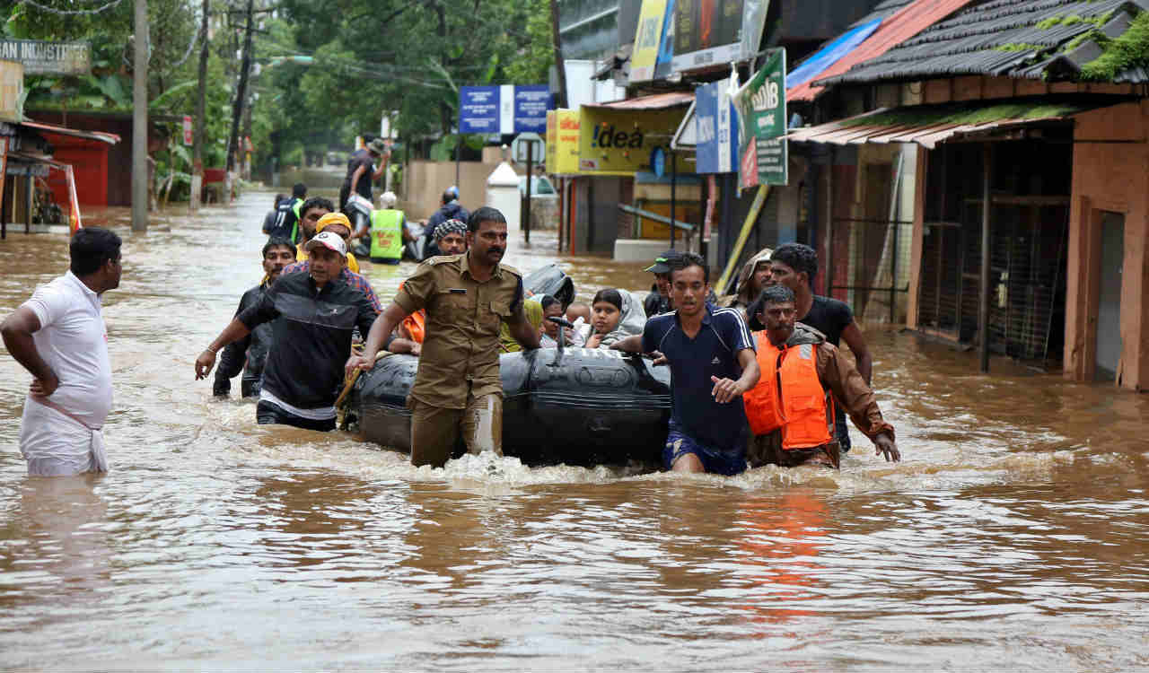 Rescuers evacuate people from a flooded area to a safer place in Aluva in Kerala. (Reuters)