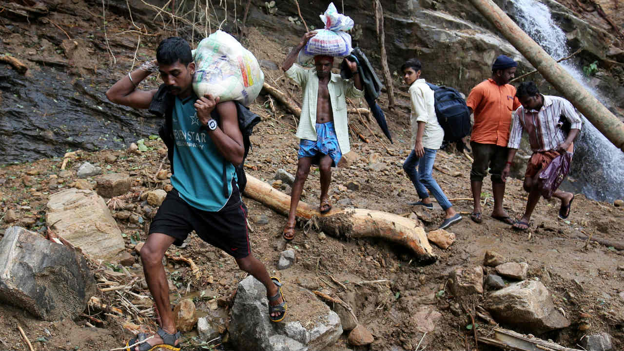 Flood victims carry relief material as they walk through a damaged area after floods, at Nelliyampathy Village. (Image: Reuters)