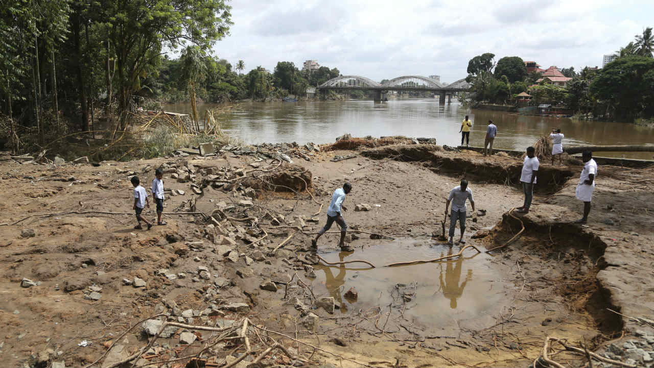 The UAE has offered Rs 700 crore fot the flood-hit state. But the Centre is unlikely to accept any foreign financial assistance. Pictured: People assessing damage caused by floods on the outskirts of Kochi. (Image: AP)