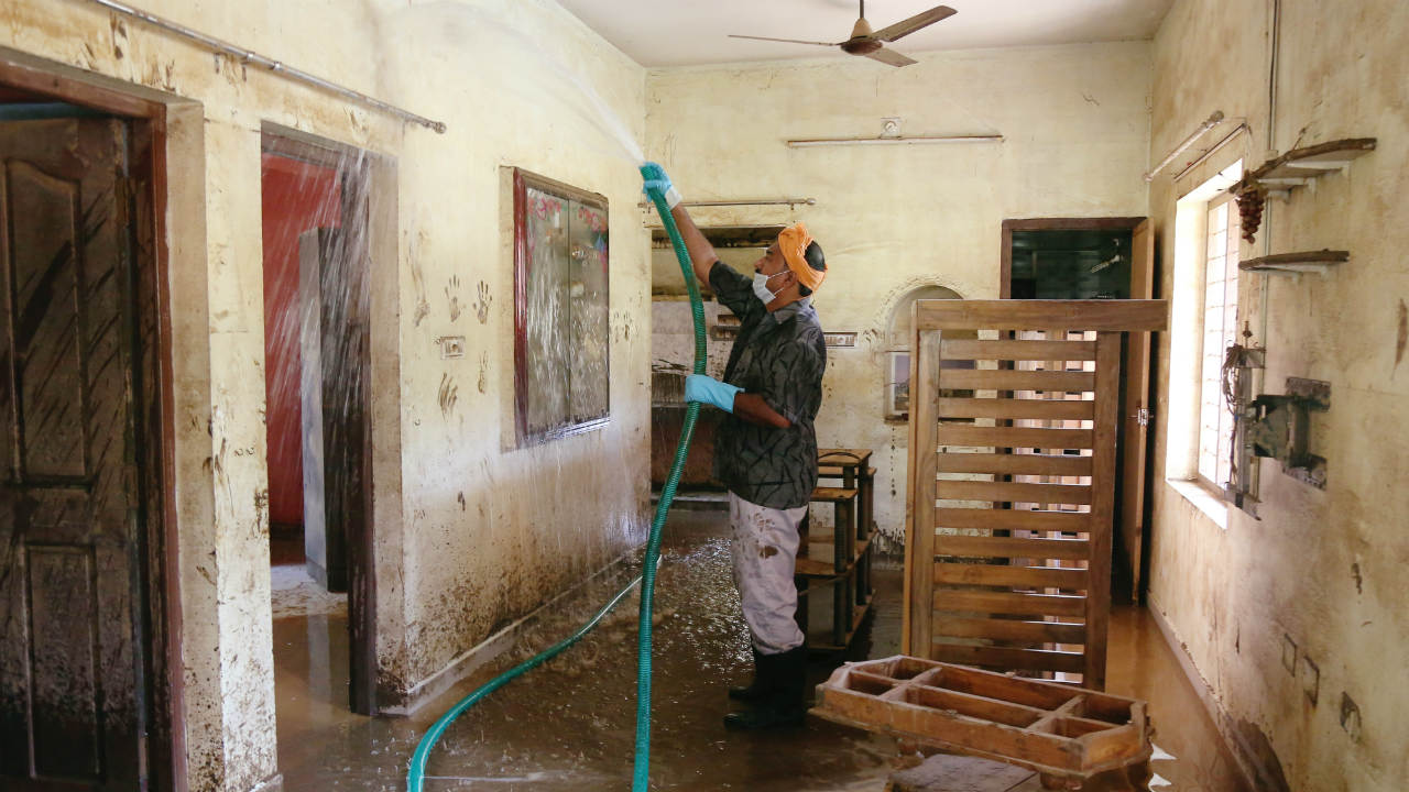 Flood water has begun receding and efforts are now on relief and recovery. Pictured: A volunteer cleaning a house following floods on the outskirts of Kochi. (Image: Reuters)