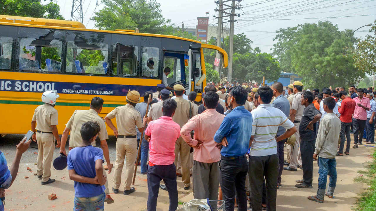 Police and public stand near the school bus that was attacked by a mob after it hit a couple while they were riding a bicycle, in Gurugram. Both the husband and wife were killed in the accident.(Photo: PTI)