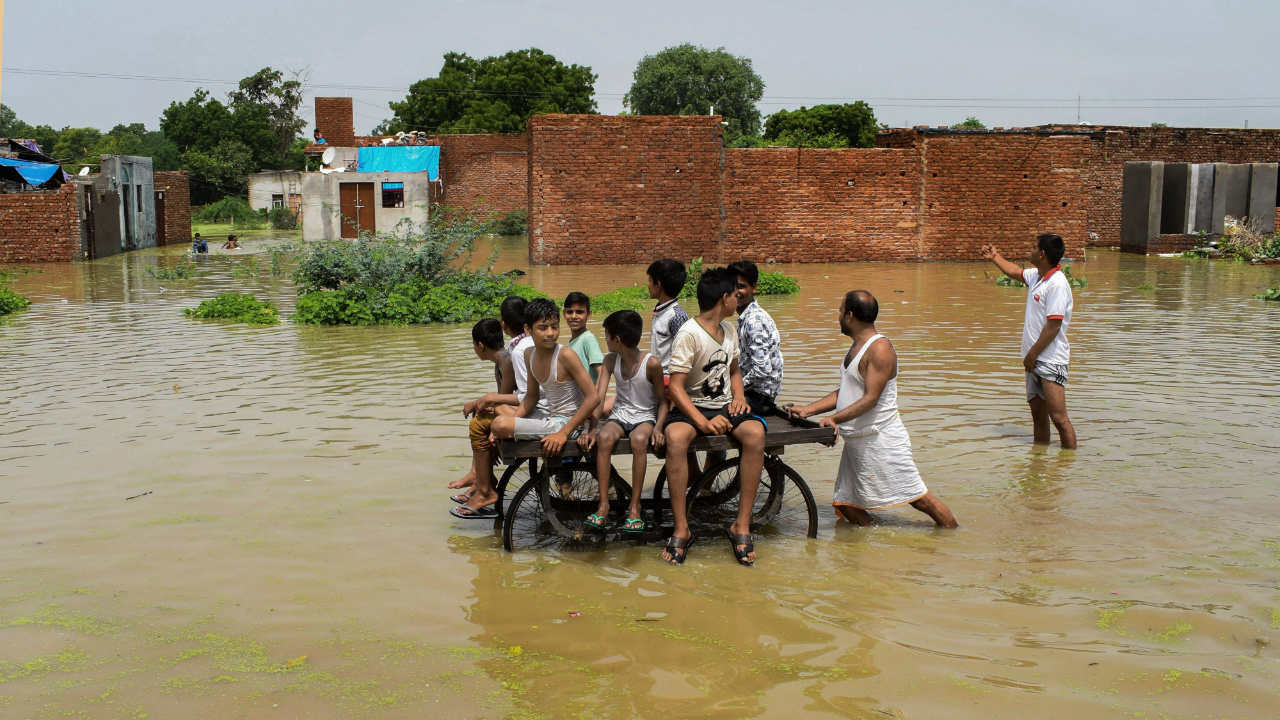 Children ride a cart as they move through a flooded colony, inundadted by the Yamuna river, in Mathura. (Photo: PTI)