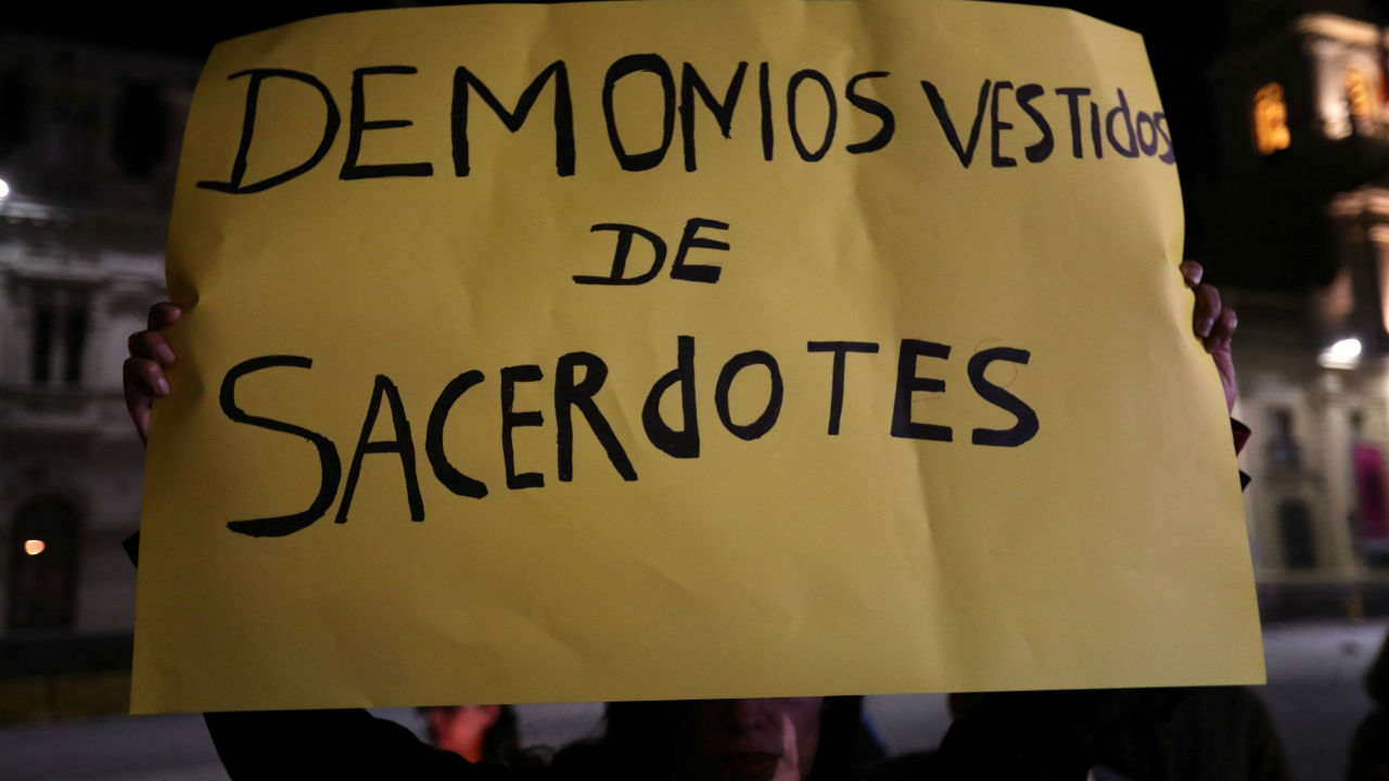 A woman holds a banner that reads 'Devils dressed as priests' during a candle vigil to protest against sexual abuse in the Chilean Roman Catholic Church outside the Santiago cathedral, in Santiago, Chile. (Reuters)