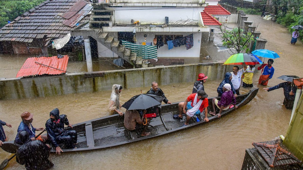 Rescue officials assist villagers out of a flooded area following heavy monsoon rainfall, near Kochi. (PTI)