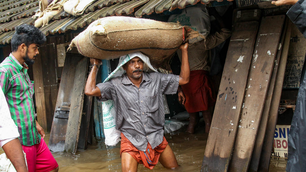 A person carries a grain sack as his house gets flooded after the Kakkayam dam was opened following heavy rains in Kozhikode. (Image: PTI)