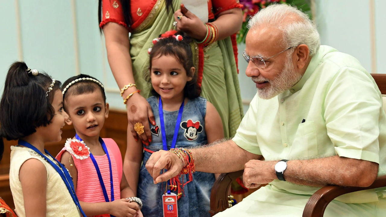 Children ties rakhi to Prime Minister Narendra Modi on the occasion of Raksha Bandhan festival, in New Delhi. (Image: PTI/PIB)
