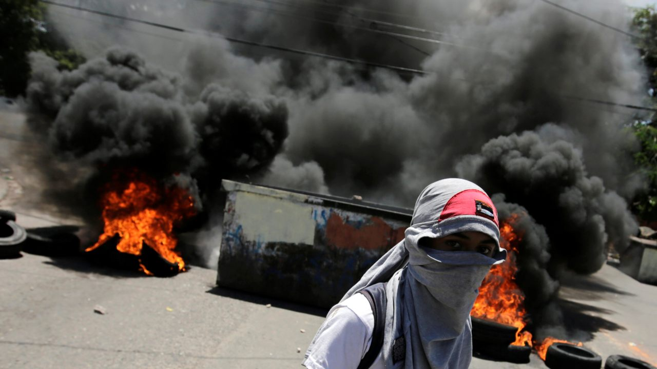 A demonstrator stands near a burning roadblock during student protests over public transportation fare increases, in Tegucigalpa, Honduras. (Reuters)
