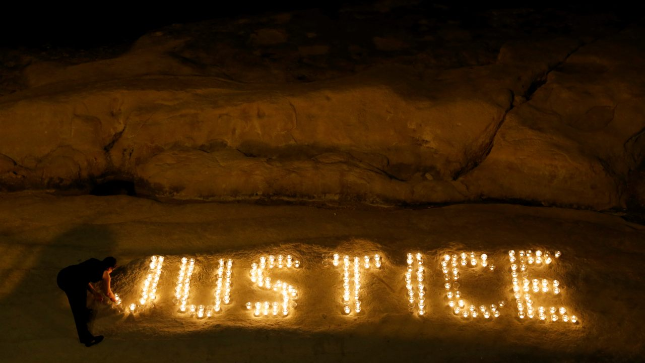 "Activists from anti-corruption group Occupy Justice light candles spelling out the word ""Justice"" to mark ten months since the assassination of investigative journalist Daphne Caruana Galizia, on a beach in Sliema, Malta. (Reuters)"