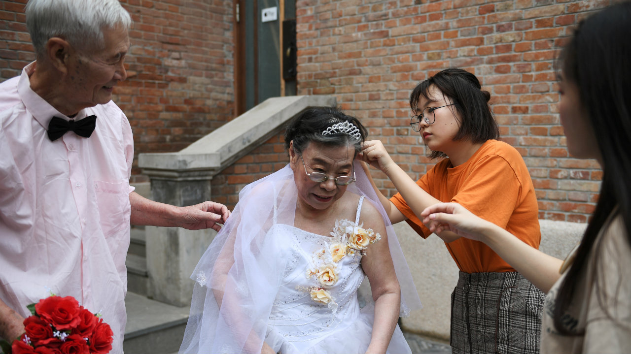 A charity volunteer helps Chen Suzhen, 82, with her veil as Chen and Chen Guozhi, 85, her husband of 60 years, attend a photo shoot event organized to recreate wedding photos for elderly couples, who have been married for more than 50 years, a day ahead of the Qixi festival, also known as Chinese Valentine's Day, in Tianjin, China. (Image: Reuters)