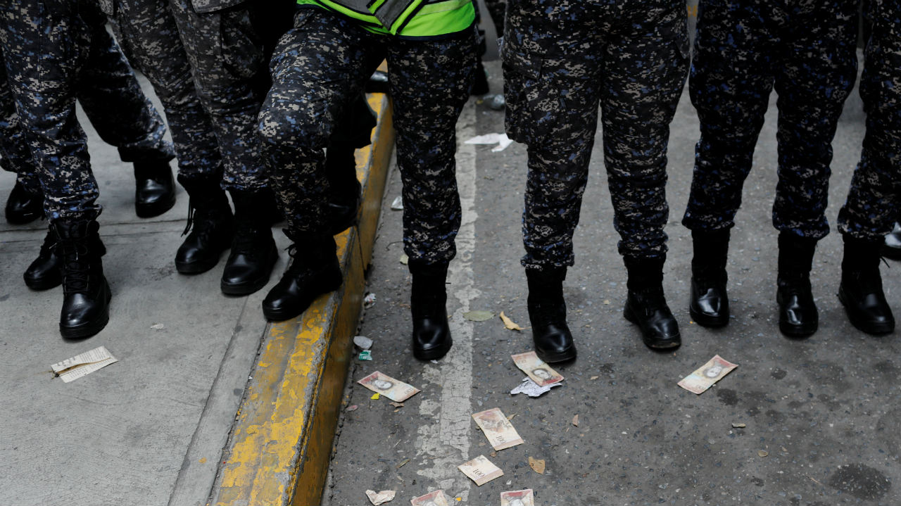 Venezuelan bolivar notes thrown by demonstrators are seen on the street in front of riot police during a protest of workers of the health sector due to the shortages of medicines and for higher wages, outside a public children hospital in Caracas, Venezuela. (Image: Reuters)