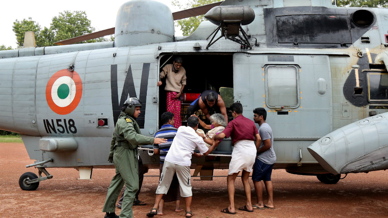 People help a woman disembark from an Indian Navy helicopter at a relief camp after being rescued from a flooded area in Kerala. (Image: Reuters)