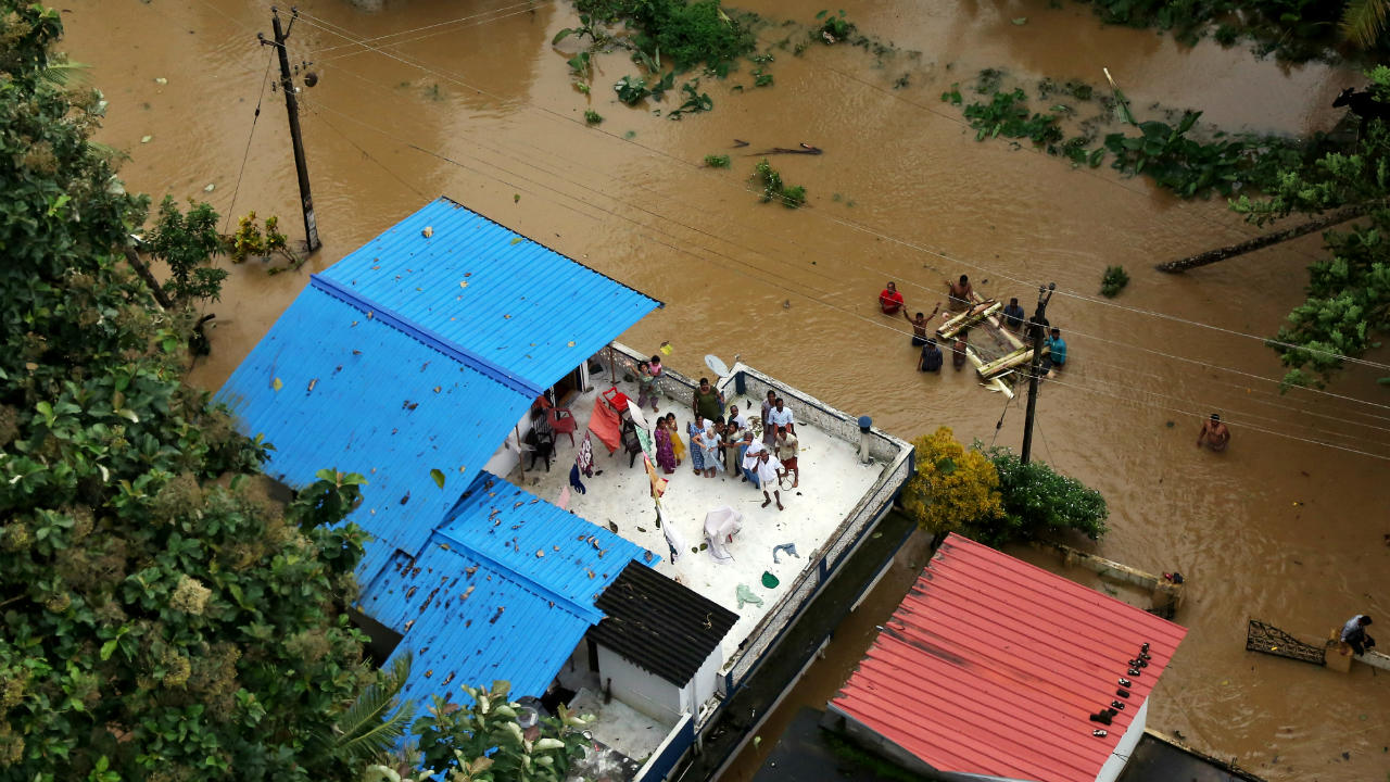 A total of 5,645 relief camps have been set up along with 3,700 medical camps across Kerala for flood victims. INS Deepak has reached Kochi with 800 tonnes of freshwater and 18 tonnes of relief material, including medicines. Pictured: People wait for aid on the roof of their house at a flooded area. (Image: Reuters)