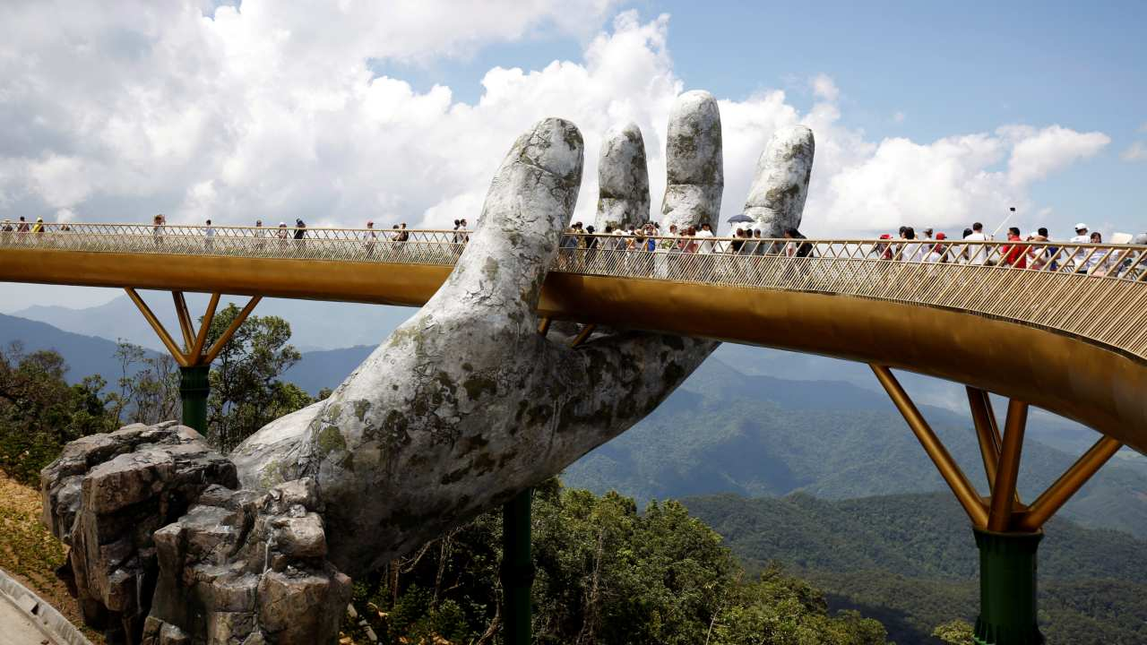 Tourists walk past giant hand structure on the Gold Bridge on Ba Na hill near Danang City, Vietnam. (REUTERS)