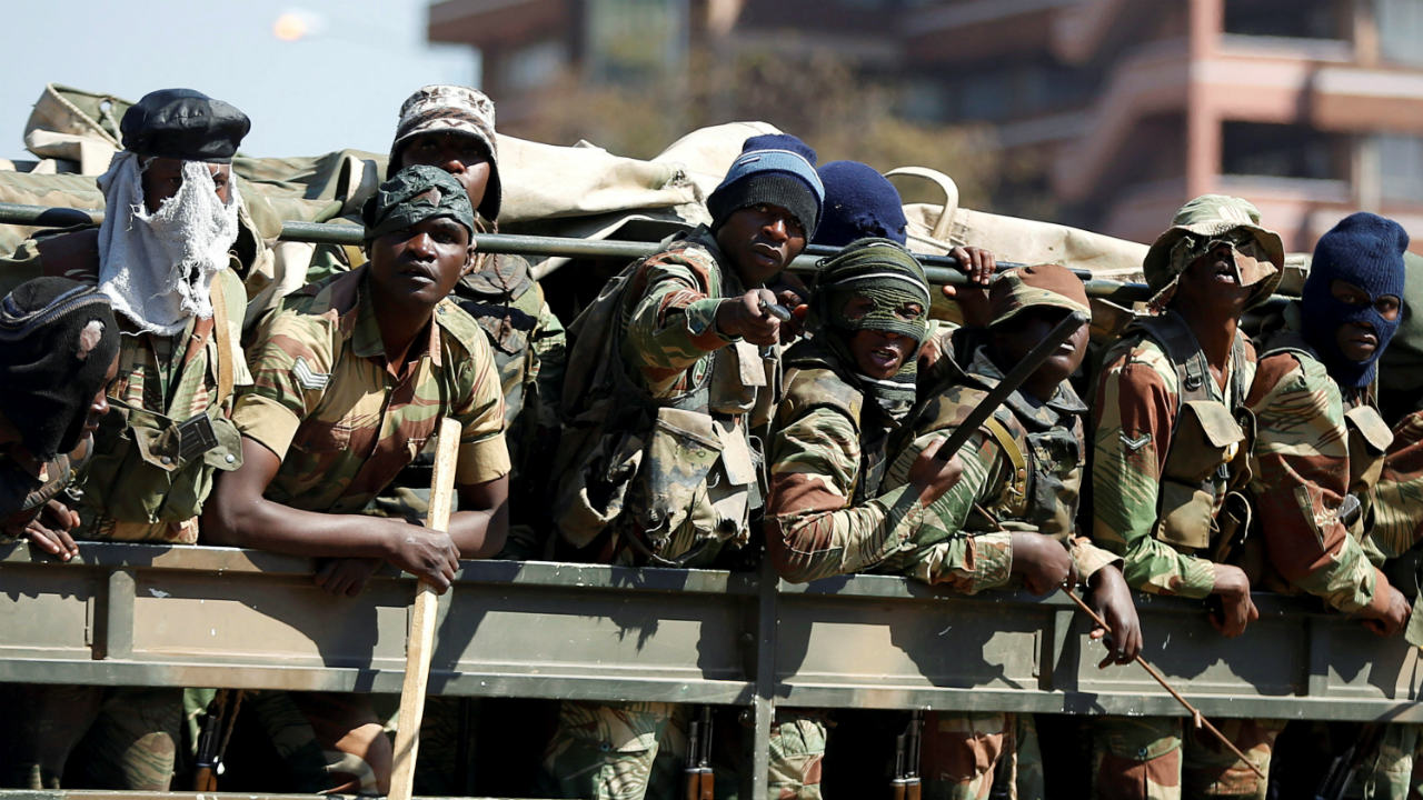 Members of the military gesture to the photographer as they patrol the streets of the capital Harare, Zimbabwe. (Image: Reuters)