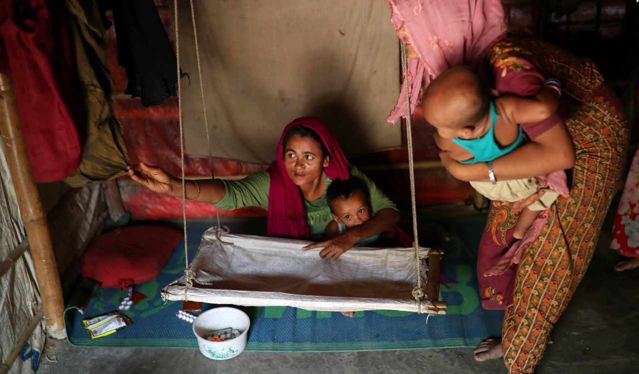Rohingya refugee women arrange a cradle for child in their makeshift tent in the Balukhali refugee camp in Cox's Bazar, Bangladesh. (Reuters)