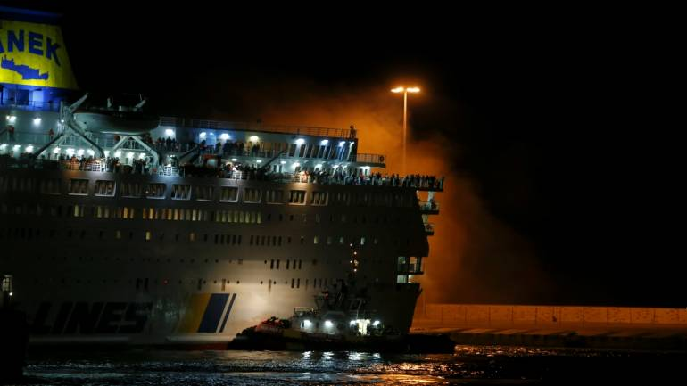 Smoke rises as passengers are seen on the deck of the Eleftherios Venizelos ferry during a fire, at the port of Piraeus, Greece. Image Source: Reuters.