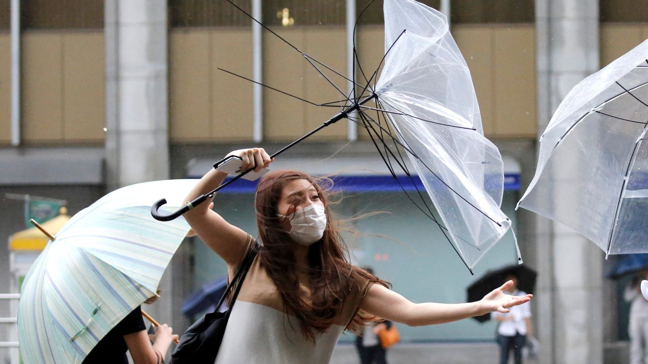 A woman using an umbrella struggles against heavy rain and wind as Typhoon Shanshan approaches Japan's mainland in Tokyo, Japan. (Image Source: Reuters)