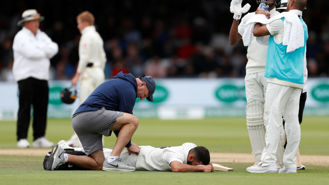 Indian skipper Viart Kohli receives treatment for his back injury on the fourth day . Kohli batted bravely through the pain before being caught by Ollie Pope at short leg on a Stuart Broad ball. (Image- Reuters)
