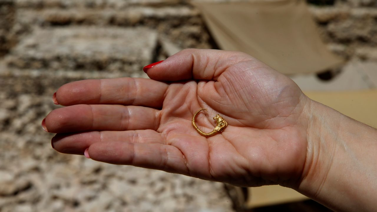 An employee of Israel's Antiquities Authority holds a gold earring believed to date back more than two millennia after being unearthed near the site of the ancient Jewish temples in Jerusalem, outside Jerusalem's Old City. (Image Source: Reuters)