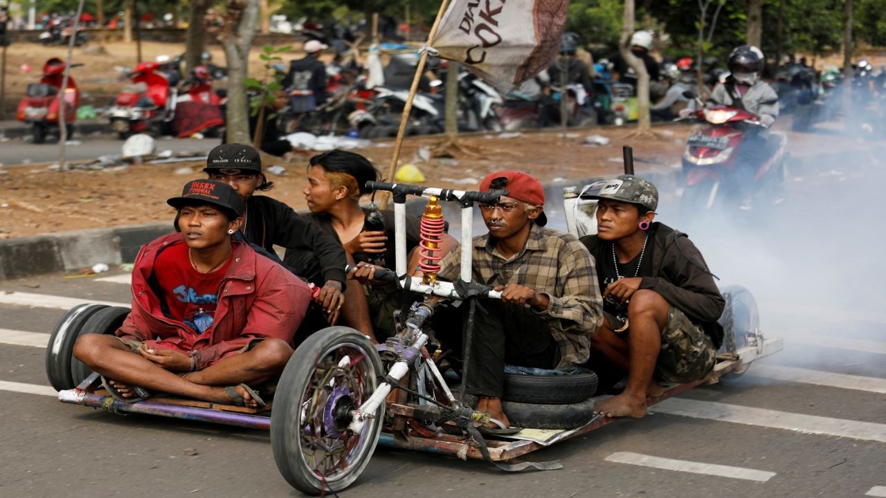 Extreme Vespa enthusiasts drive their bike near the site of a weekend festival for extreme Vespas in Semarang, Central Java, Indonesia. (Image Source: Reuters)