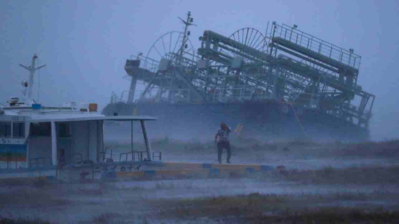 In this photo, a vessel, rear, tilts on one side as it ran ashore at a pier as a typhoon approached Yonabaru, Okinawa prefecture, southern Japan. A powerful typhoon is ripping through Japan and authorities are warning people to brace for heavy winds and rain in areas that include those devastated by a previous storm. (AP/PTI)