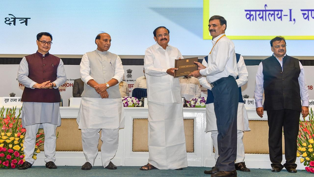 Vice President Venkaiah Naidu honours Astt Director (Rajbhasha Head-office) S P Tiwari as Home Minister Rajnath Singh, MoS for Home Affairs Kiren Rijiju look on, during the Hindi Diwas Samaroh 2018, in New Delhi. (Image:PTI)