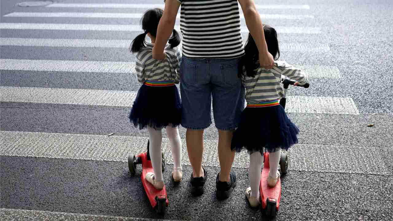 A father crosses a road with his twin daughters in Shanghai, China. (Reuters)