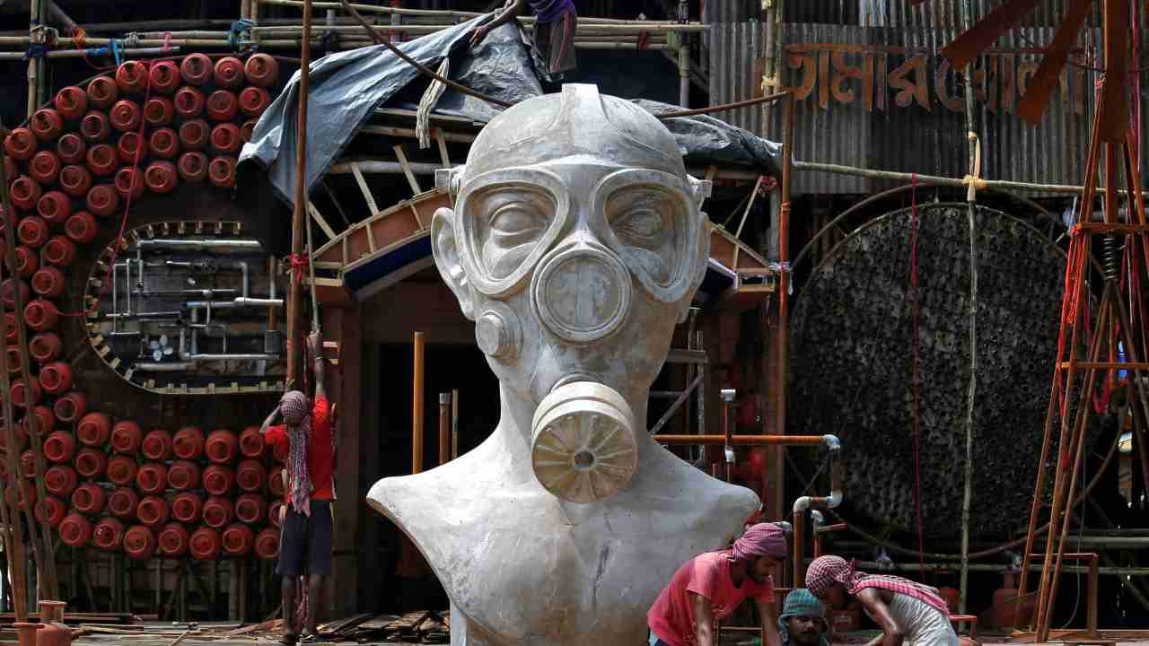 "Labourers work in front of a giant sculpture of a man wearing a gas mask that will be used to decorate an ""Open Air"" themed pandal (temporary platform) for the upcoming Hindu festival of Durga Puja in Kolkata, India. According to organizers, the theme of the pandal seeks to create awareness on the importance of clean, unpolluted air, to devotees of Goddess Durga. (Reuters)"