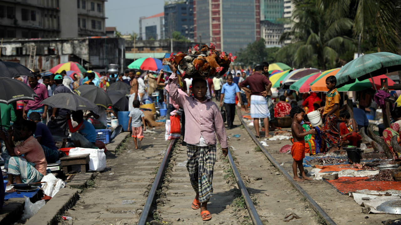 A chicken seller walks along the railway track in Dhaka, Bangladesh. (Image: Reuters)