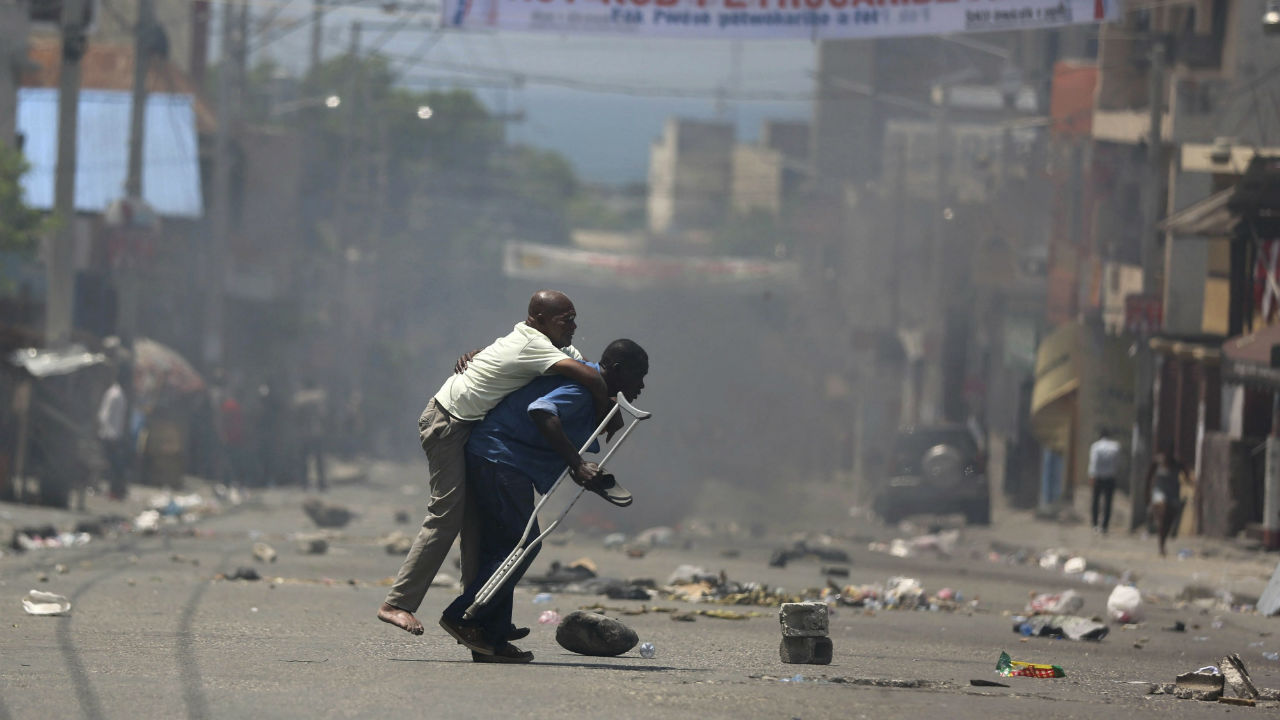 A handicapped man is carried across the street amid police firing tear gas at protesters who are demanding to know how PetroCaribe funds have been used by the current and past administrations, in Port-au-Prince, Haiti, Sunday. (Image: AP/PTI)