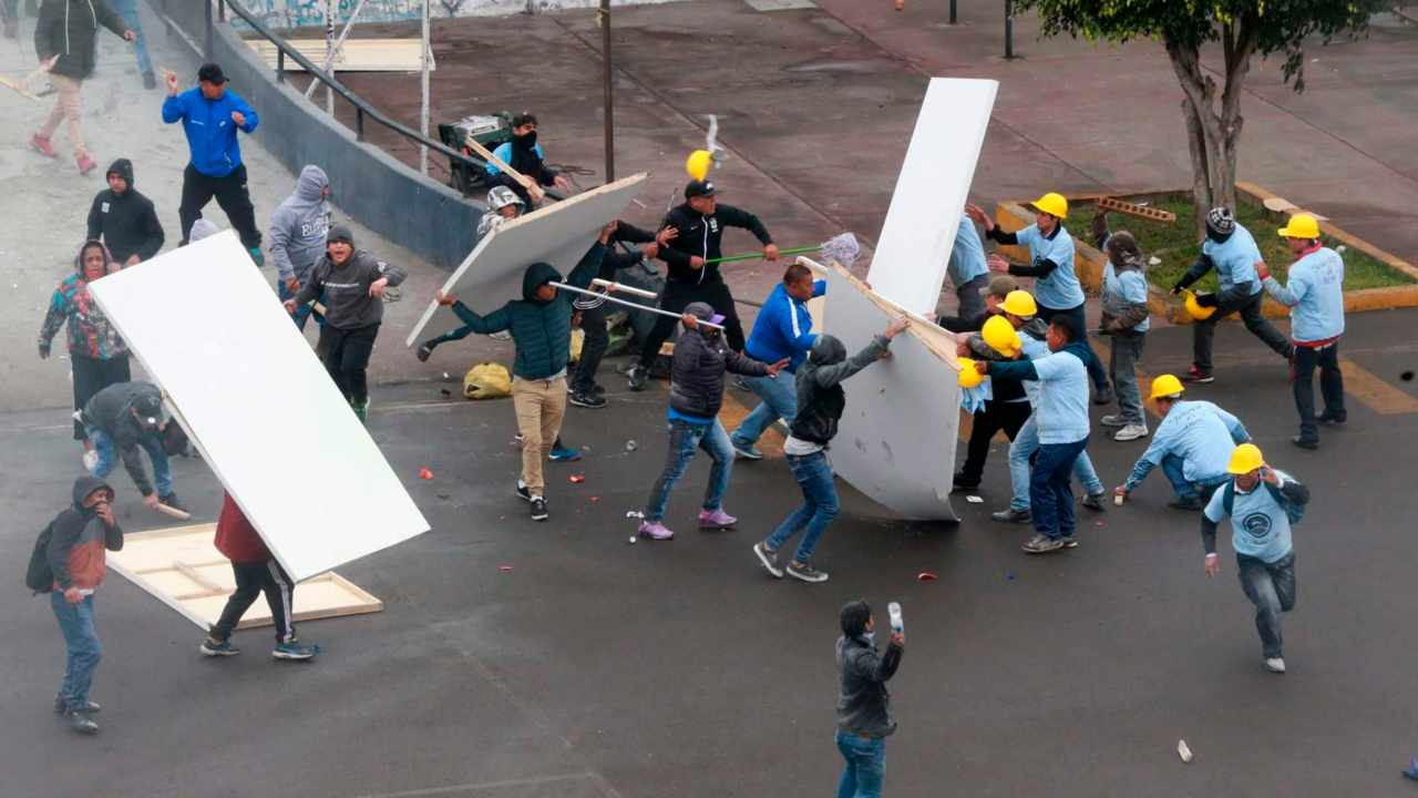 Alianza Lima club soccer fans, left, fight with members of an evangelical church, yellow helmets at right, outside the soccer club's stadium in Lima, Peru. The two groups clashed outside the stadium over who has the right to use the area surrounding the sports venue, after the religious group arrived early in the morning and started removing the team's logos from the parking area.  (Image: AP/PTI)