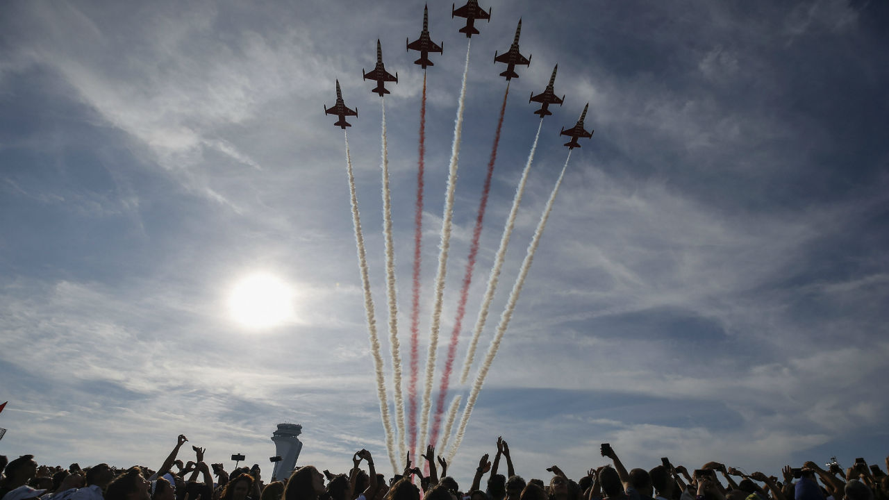 Members of the crowds cheer and take photographs as 'Turkish Stars', F-5 fighter airplanes, the aerobatic team of the Turkish Air Force, fly in formation over Istanbul's new airport, during the Teknofest aviation, space and technology fair in Istanbul, Turkey. (Image: AP/PTI)