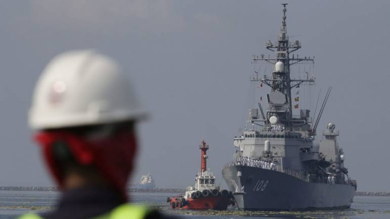 A Filipino port worker looks as the Japanese Ship Akebono (DD-108), a Murasame-class destroyer of the Japan Maritime Self-Defense Force, prepares to dock at Manila's south harbor, Philippines. The JS Akebono is in the country for a three-day goodwill visit. (AP/PTI)