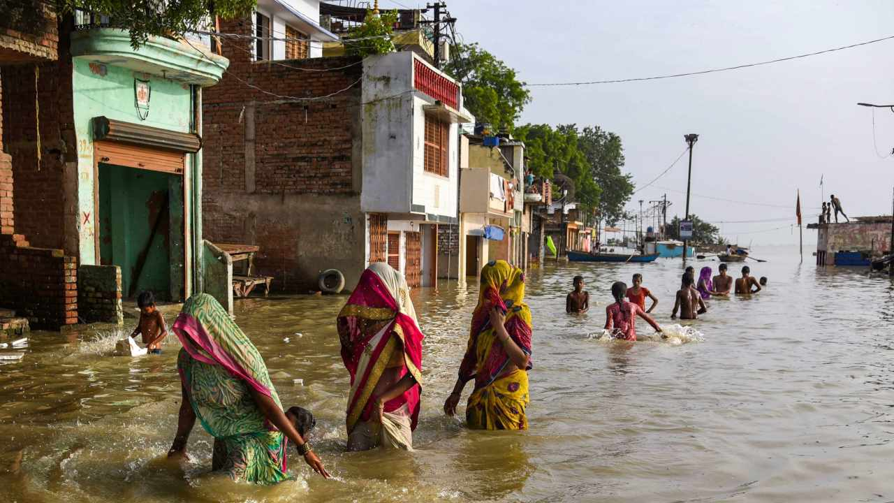 People move to safer places after water level of river Ganga rose creating a flood-like situation at Daraganj, in Allahabad. (Image: PTI)