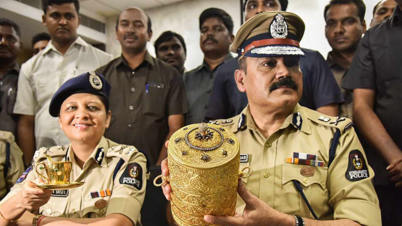 Police Commissioner Anjani Kumar along with a senior police officer shows to media the three-tier golden tiffin box and a golden cup after their recovery, in Hyderabad. The historic priceless objects went missing from the Nizam Museum at Purani Haveli. (Image: PTI)